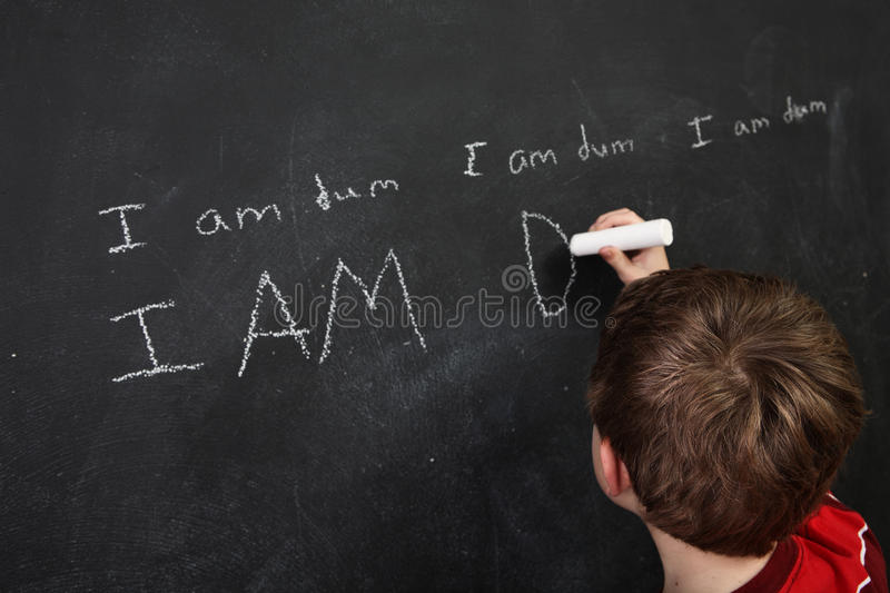 Boy with poor spelling and low self esteem writing on a blackboard royalty free stock photo