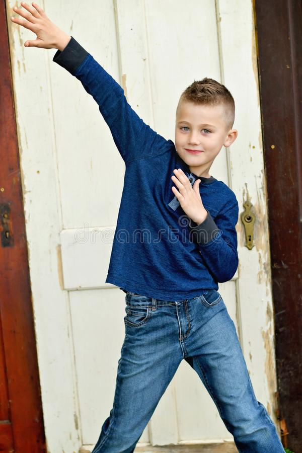Boy posed portrait. Boy holding hands in a funny posed position with wooden for backdrop royalty free stock image