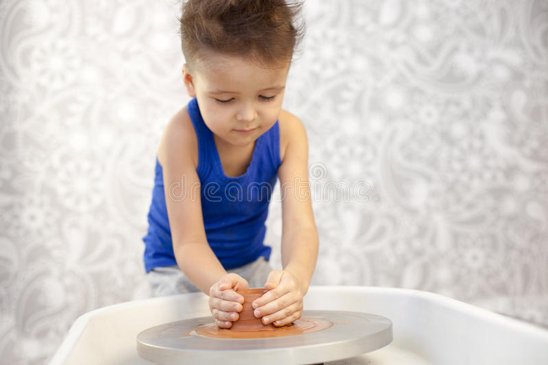 Boy potter at work. In the studio royalty free stock photography