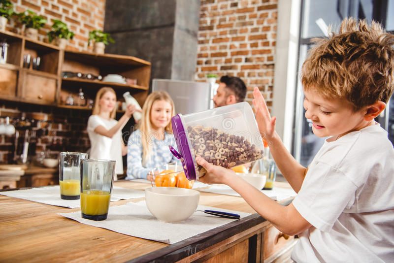 Boy pours corn flake rings. Little boy pours corn flake rings in bowl in kitchen royalty free stock images