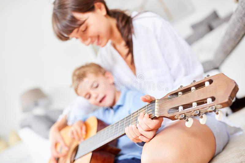 Boy is practicing playing the guitar royalty free stock photo