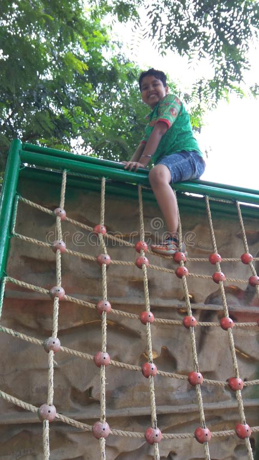 Boy practicing rope climbing in garden area. Boy practicing wall and rope climbing in garden area with artificial supports embossed on it. other side having stock images