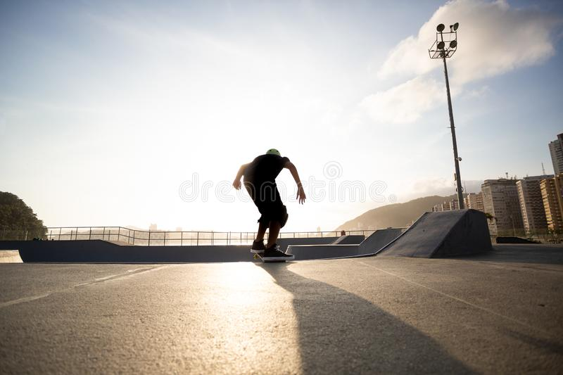 Boy practicing skateboarding during the sunset stock images