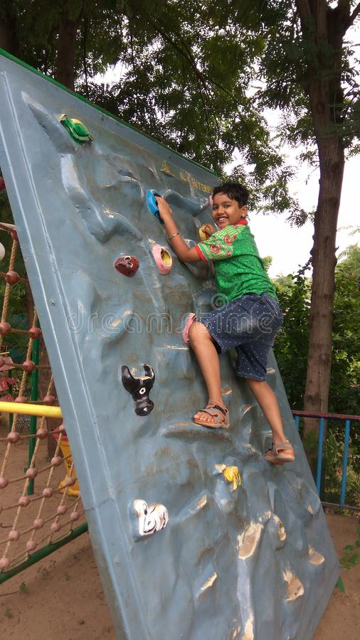 Boy practicing wall climbing in garden area. With artificial supports embossed on it. other side having rope nets to climb down stock image