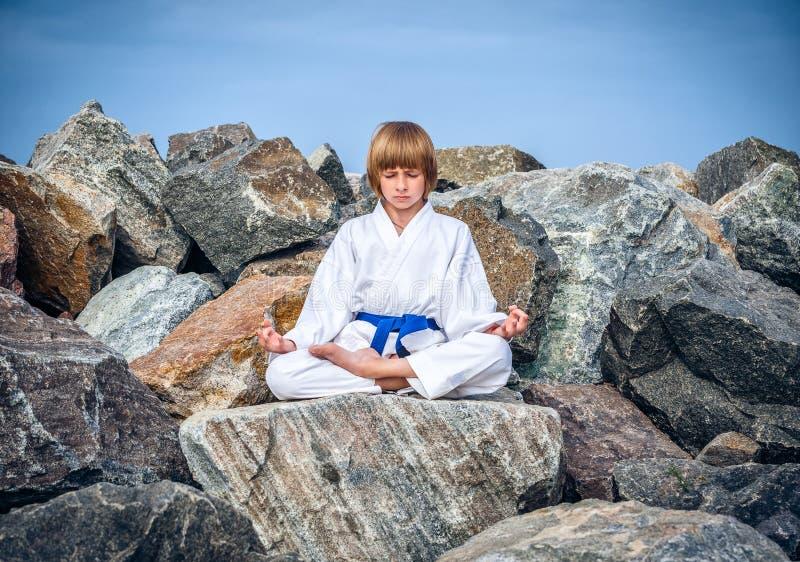 Boy practising yoga on beach royalty free stock image