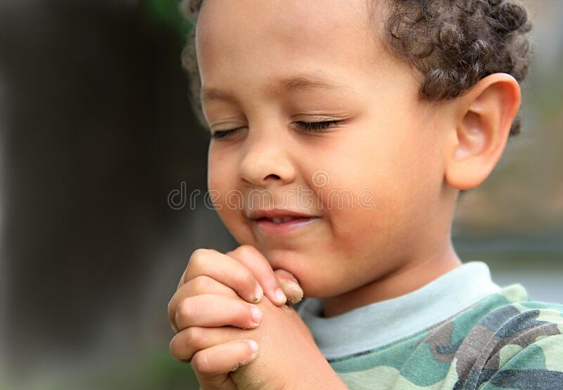 Boy praying to God with hands held together stock photo royalty free stock photos