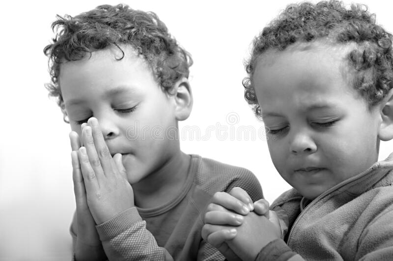 Boy praying to God with hands held together stock photo royalty free stock images