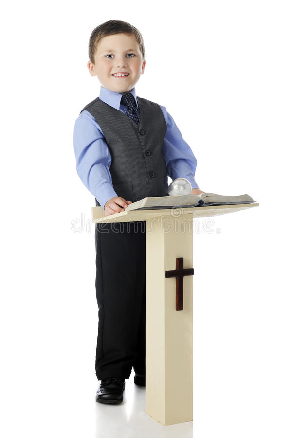 Boy Preacher. A dressed up elementary boy smiling from his post behind a Christian pulpit holding an opened Bible. On a white background royalty free stock images