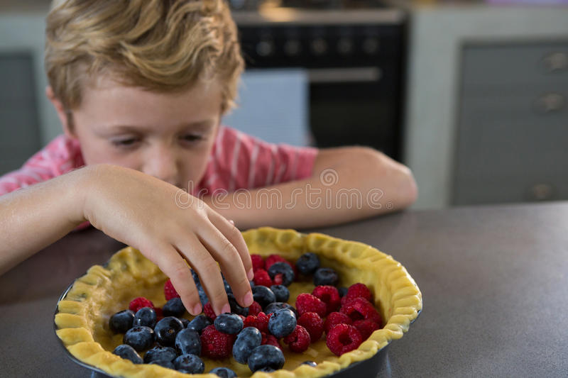 Boy preparing tart with berries in kitchen stock photography