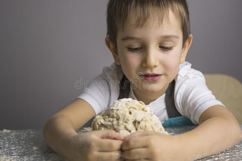 Boy is prepearing pizza dough stock image