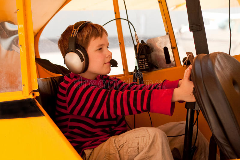 Boy pretends to fly Piper Cub airplane. A cute little nine-year-old boy is in the cockpit of a 1946 yellow Piper Cub airplane. He pretends to fly the aircraft as royalty free stock images