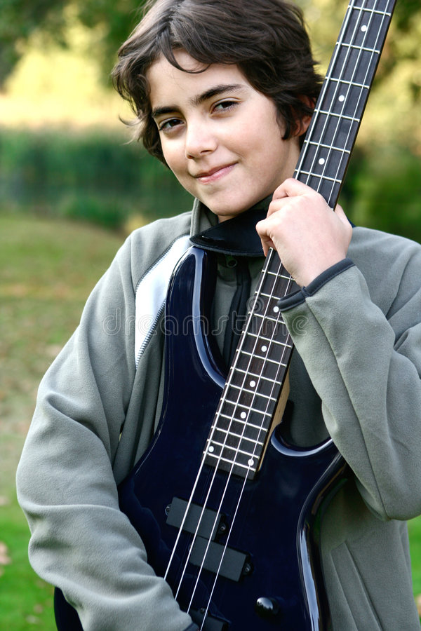 Boy proudly showing off his accoustic guitar. Young boy proudly showing off his accoustic guitar stock images