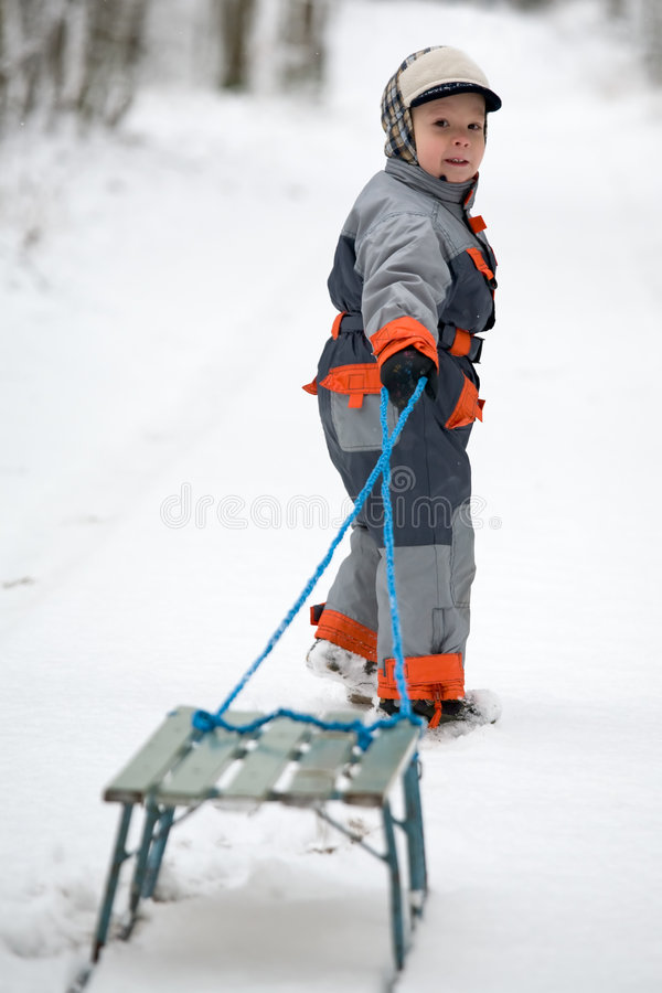 The boy is pulling old sledges stock images