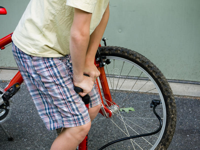 Boy pumping up a bike tire. A boy pumping air into his bike tire stock photos
