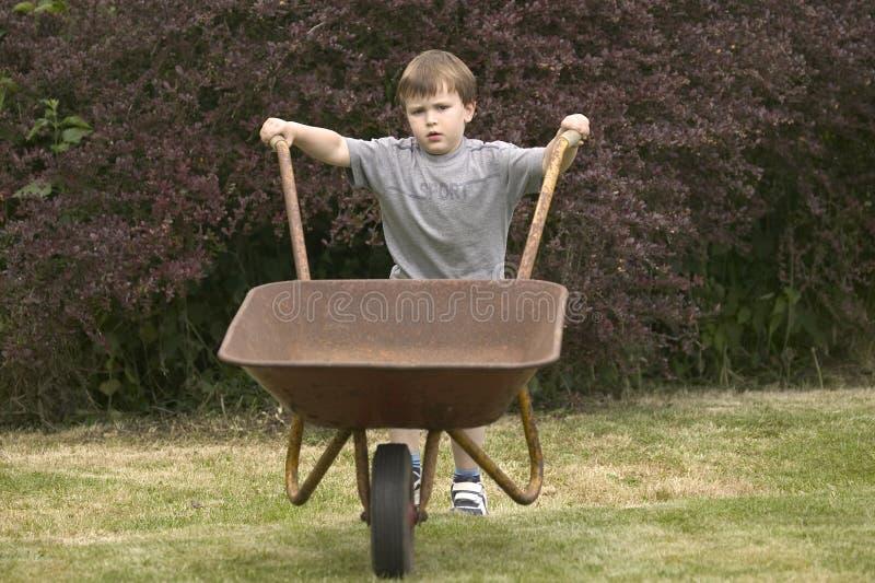 A boy pushing a wheelbarrow stock photo