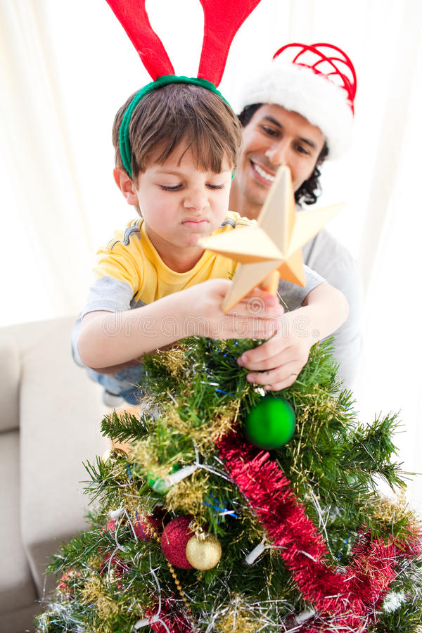 Download The Boy Put A Star On The Top Of A Christmas Tree Stock Image - Image: 11943341