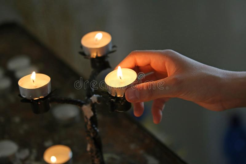 Boy puts a candle with his hand stock photos
