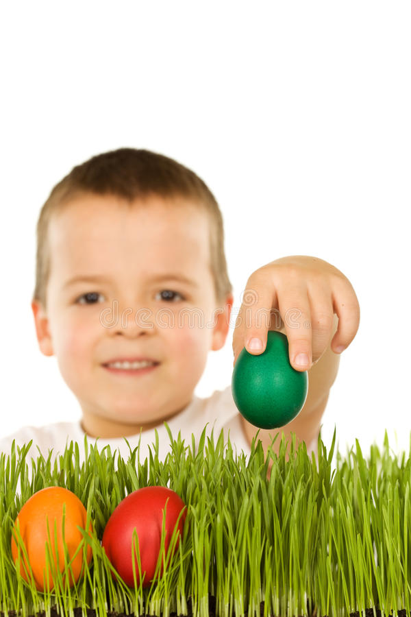 Boy putting easter eggs in the grass