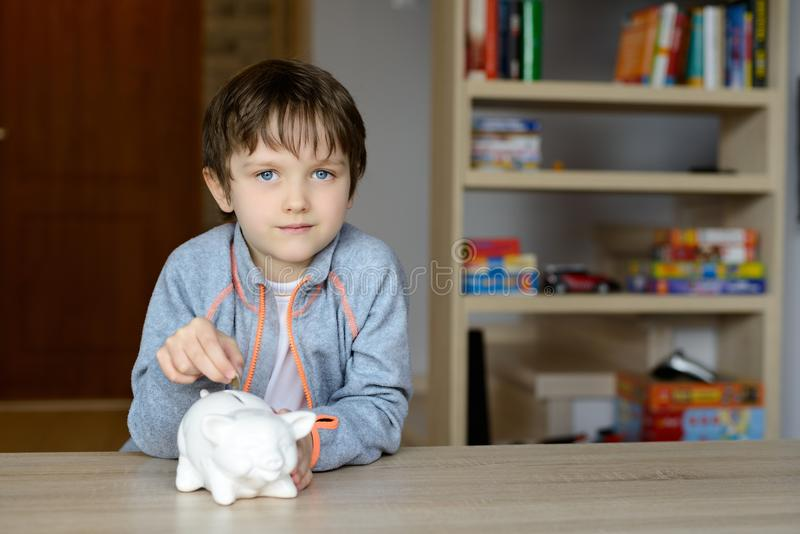 Boy putting the 1 euro coin to his piggy bank. Little boy putting the 1 euro coin to his piggy bank in the living room royalty free stock photo