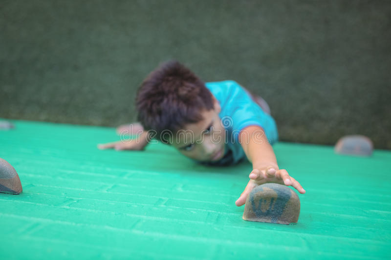 Boy reaching climbing holds on wall. High angle view of boy reaching climbing holds on wall royalty free stock images
