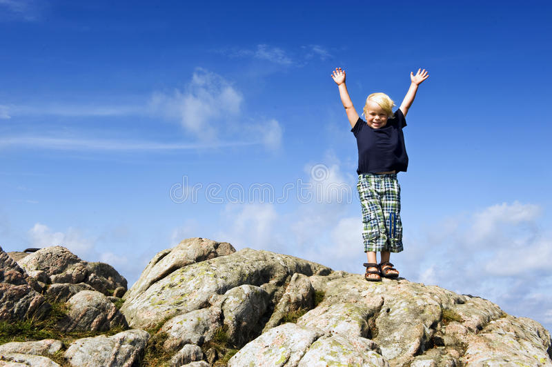 Boy reaching top. Young boy with his arms raised in victory on top of a rock, conceptual image for conquering challenges, pushing the boundaries, and continuous stock photo