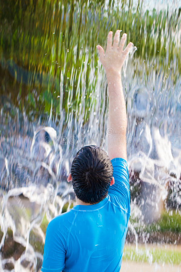 Boy reaching up to feel water in a waterfall stock photos
