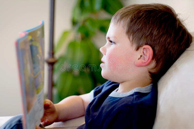 Boy reading. Young boy sitting on a sofa reading royalty free stock photography