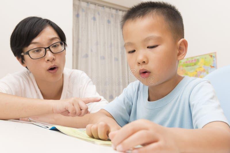 Boy reading aloud with tutorship royalty free stock photo
