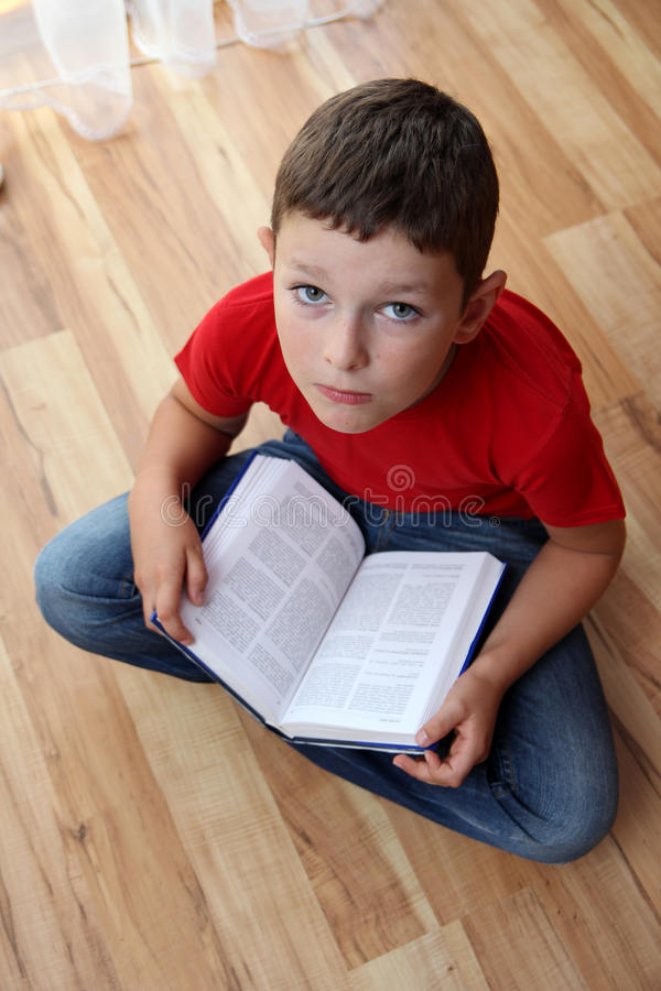 Boy reading book stock photography
