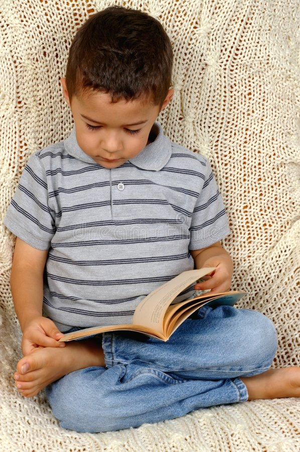 Boy Reading a Book. Portrait of a young boy sitting on a crocheted afghan blanket reading a book royalty free stock photos