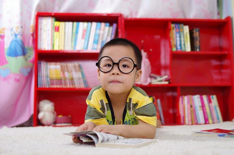Boy reading book on floor stock photos
