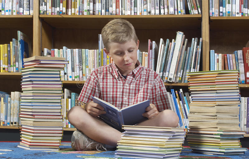 Boy Reading Book In Library stock photo