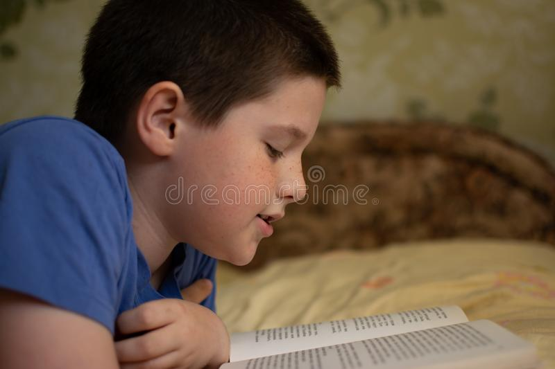 Boy reading a book lying on the bed royalty free stock image