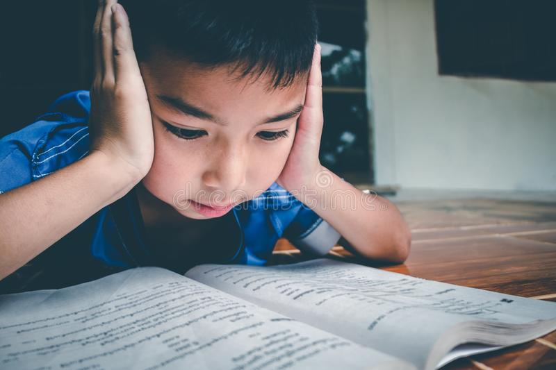 The boy is reading the book for prepare the exam on this coming Monday stock photos