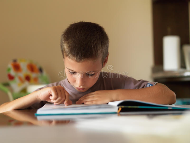 Boy reading a book while sitting at table at home. stock image