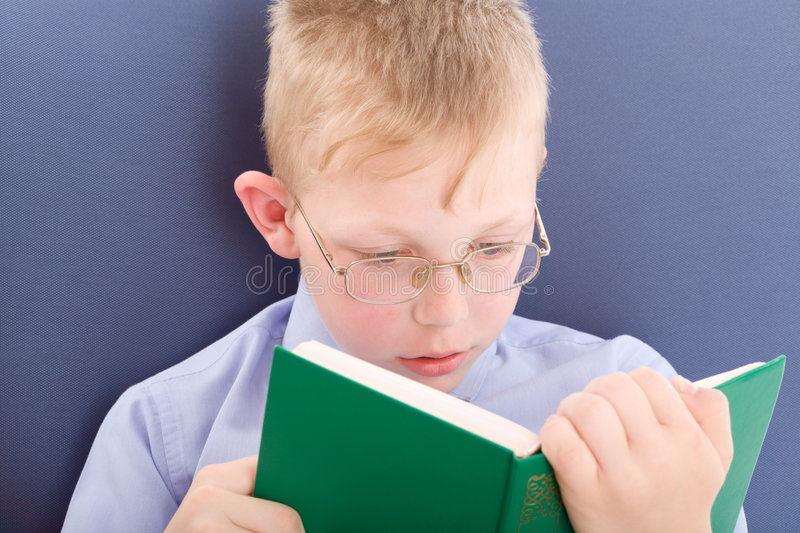 Boy reading interesting book stock images