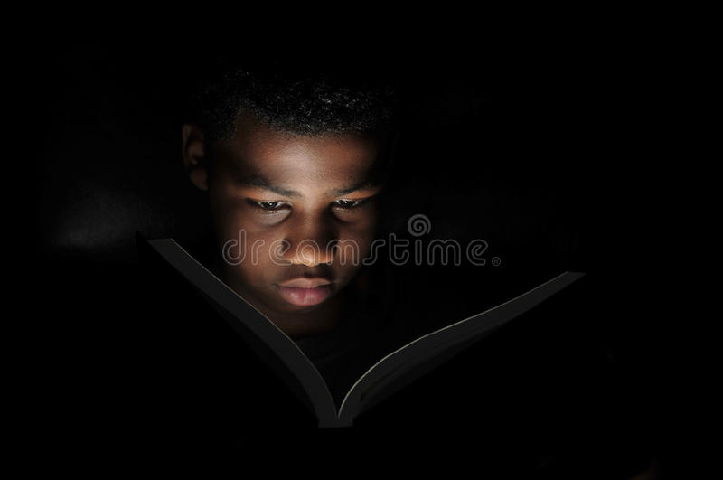 Boy reading at night. Portrait of black boy with illuminated face reading book at night stock images