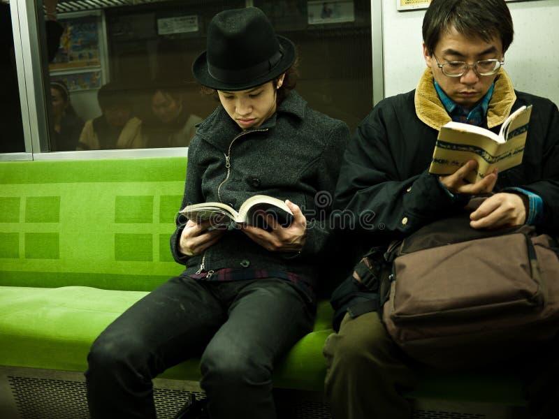 Boy reading in subway stock photo