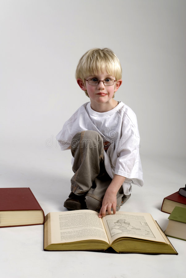 Boy is reading thick books. A smart young boy is reading thick books stock photos