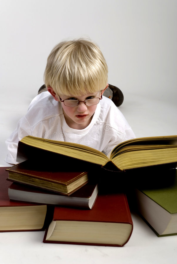 Boy is reading thick books. A smart young boy is reading thick books royalty free stock photos