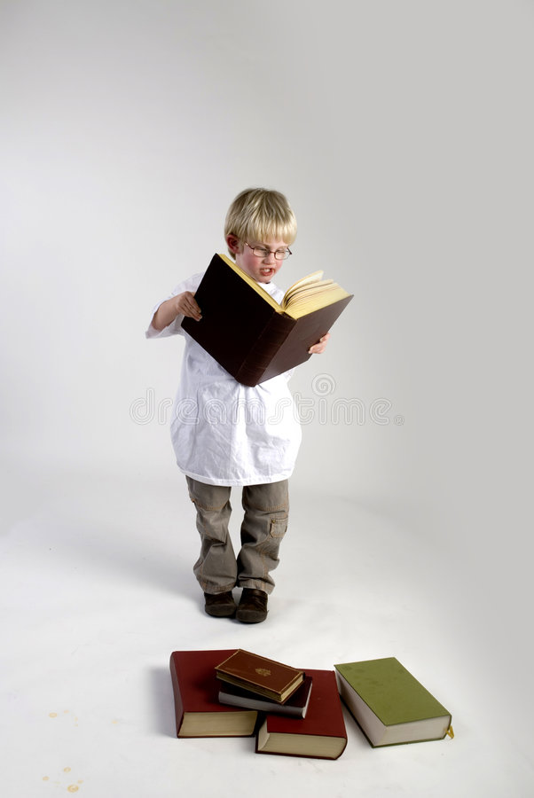Boy is reading thick books. A smart young boy is reading thick books stock image