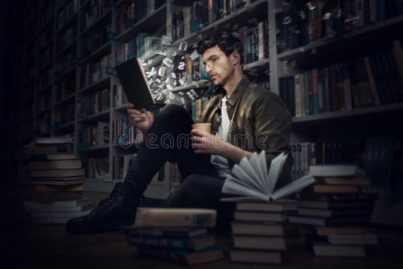 Boy reads a book in a library. Concept of curiosity, imagination and culture royalty free stock photos