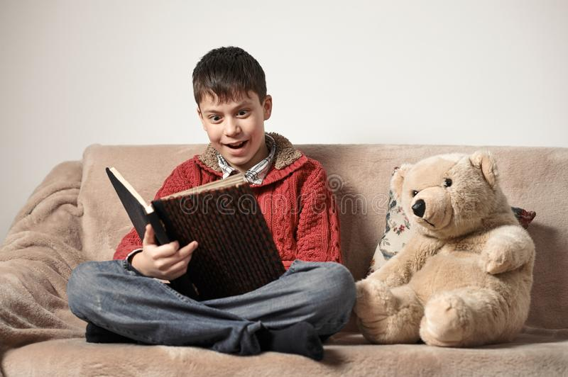 Boy reads a book, sits on the sofa with a bear toy stock photography