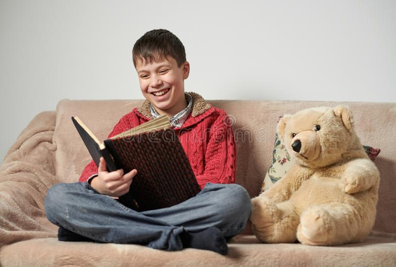 Boy reads a book, sits on the sofa with a bear toy royalty free stock images