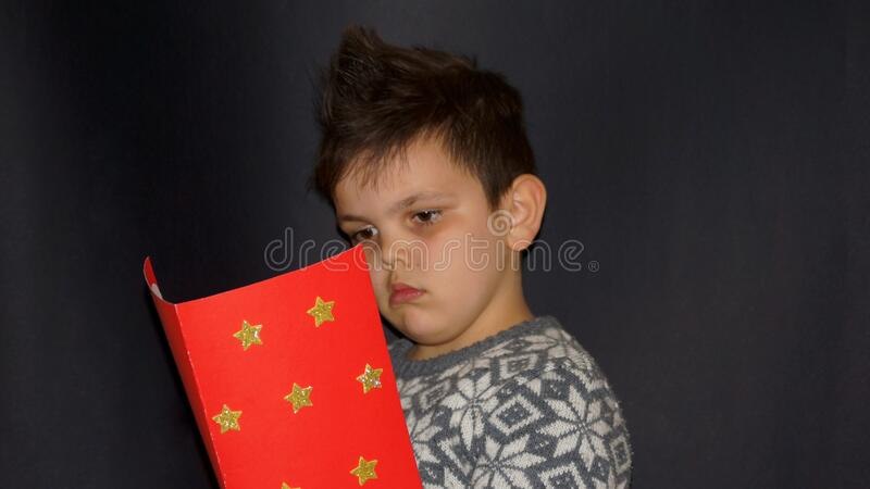 The boy reads his humane work. Boy with modern hairstyle, modern boy hairstyle, humane work, black boy, little boy. human face royalty free stock image