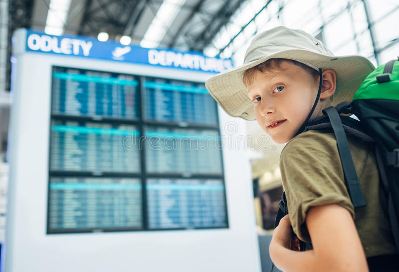 Boy ready for journey near the departure information desk in air stock photo