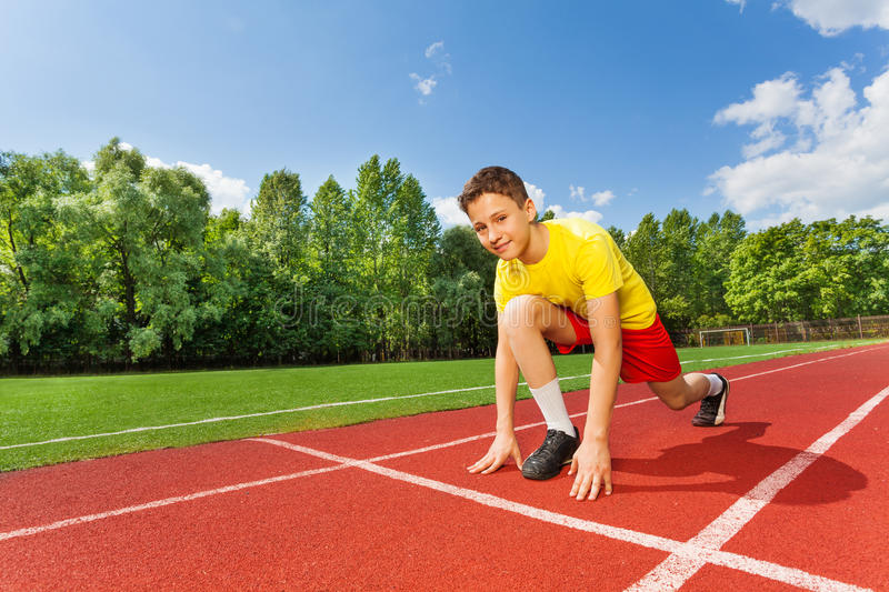 Boy in ready position on one bend knee to run. Smiling boy in ready position on one bend knee to run marathon in summer royalty free stock images