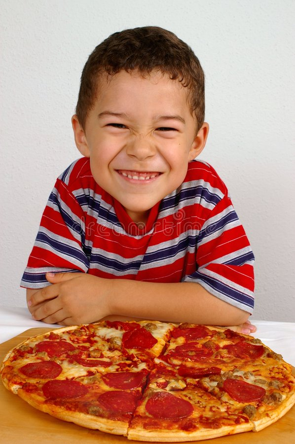 Boy ready to eat a pizza. A handsome young smiling boy ready to eat a pepperoni and sausage pizza stock photo