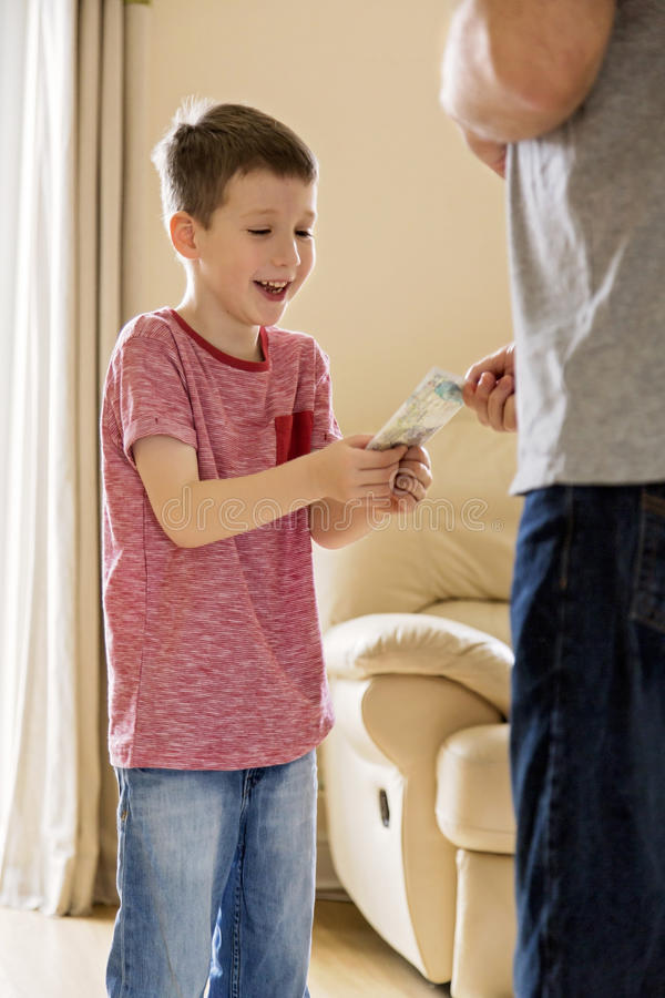 Boy receiving pocket money (allowance) from father. Father gives pocket money (allowance) to son royalty free stock images