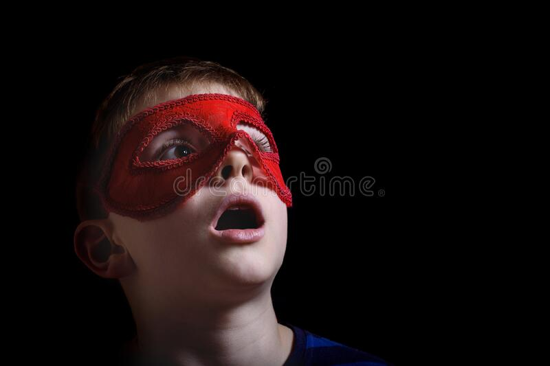Boy in red carnival mask on black background. Portrait closeup isolated. Boy in red carnival mask on black background. Surprise and admiration. Portrait closeup royalty free stock images
